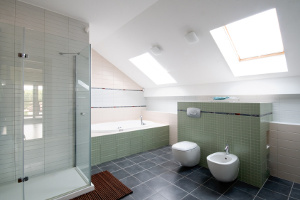 Modern bathroom with pale green tiles, large shower and bathtub.